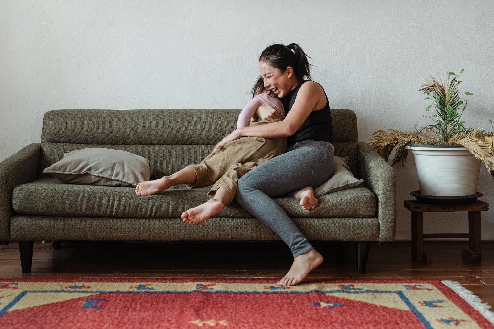 Young mother playing with her child on the couch